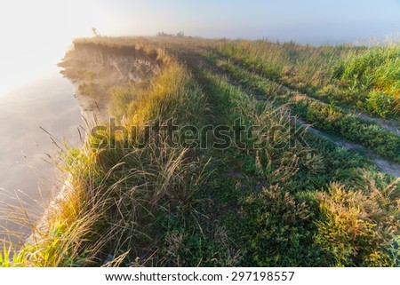 Fantastic foggy river with fresh green grass in the sunny beams. Dramatic colorful scenery. Ukraine, Europe. Beauty world. - stock photo