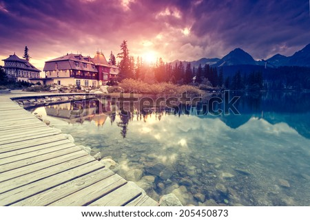 Fantastic mountain lake with berth in National Park High Tatra. Dramatic overcast sky. Strbske pleso, Slovakia, Europe. Beauty world. Retro style filter. Instagram toning effect. - stock photo