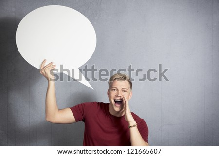 Fantastic news: Joyful man shouting great news while holding white blank speech bubble with space for text isolated on grey background. - stock photo