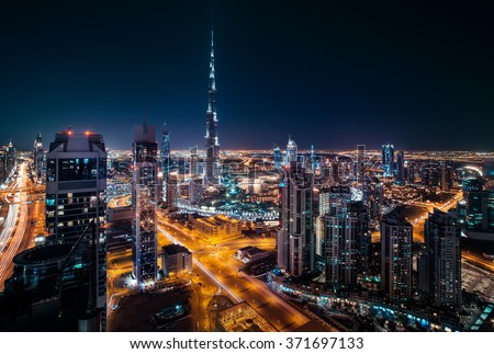 Fantastic rooftop view of Dubai's modern architecture by night with illuminated skyscrapers.  - stock photo