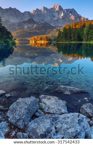 Fantastic sundown on mountain lake Eibsee, located in the Bavaria, Germany. Dramatic unusual scene. Alps, Europe. - stock photo