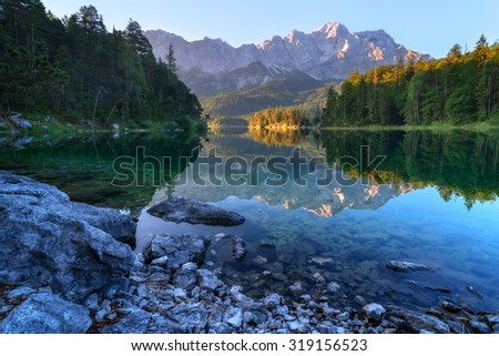 Fantastic sundown on mountain lake Eibsee, located in the Bavaria, Germany. Dramatic unusual scene. Alps, Europe. - stock photo