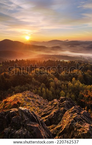 Fantastic sunrise on the top of the rocky mountain with the view into misty autumn valley - stock photo