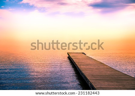 fantastic tranquil scene of a pier in the sea with fog and the sky above - stock photo
