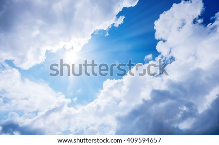 Fantasy blue sky with dramatic clouds under shrining sun light - stock photo