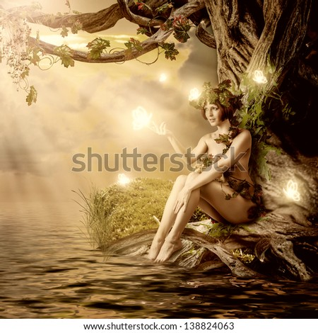 Fantasy fairytale beautiful woman - wood nymph or dryad sitting about water and big old tree - stock photo