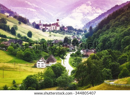 Fantasy landscape with mountain village and old church in Germany, St. Trudpert, Muenstertal, Black forest - stock photo