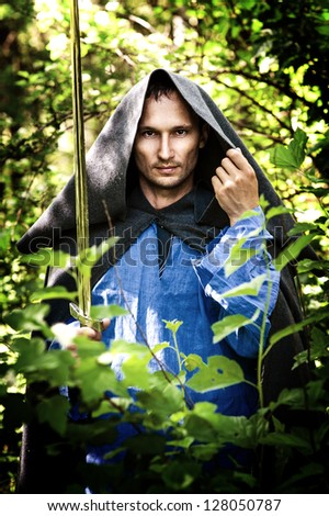 Fantasy picture of handsome mystery man with medieval sword - stock photo