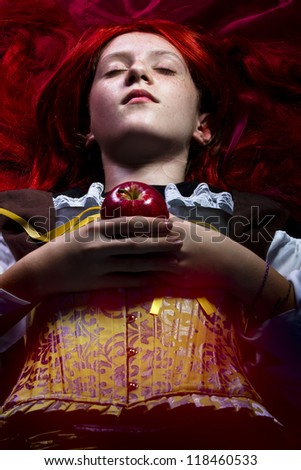 fantasy portrait of the beautiful lying Snow White with an apple - stock photo