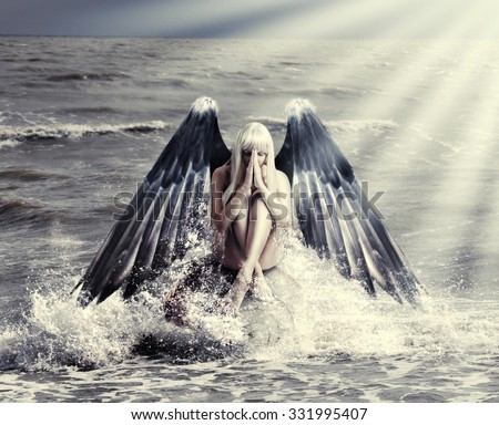 Fantasy portrait of woman with dark angel wings praying while sitting in  spray of  sea during storm - stock photo