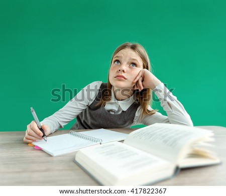 Fantasy pupil looking up as if daydreaming or thinking of something, while sitting at the desk with open book. Photo of teen school girl, creative concept with Back to school theme - stock photo