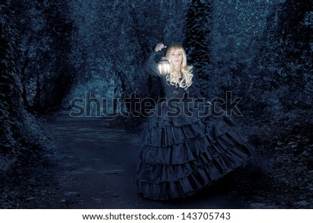 Fantasy woman traveling at night with a lantern - stock photo