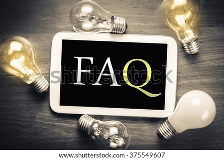 FAQ (Frequently Asked Question) topic on mobile tablet with glowing light bulbs on the table - stock photo