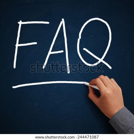 FAQ written on blue chalkboard with white chalk in hand. - stock photo