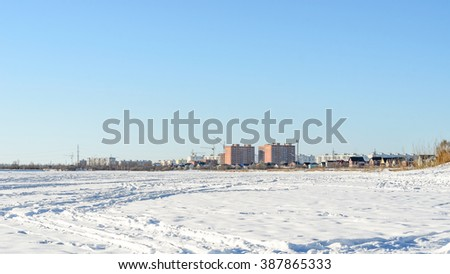 Far lake shore with houses in the distance during the day. - stock photo