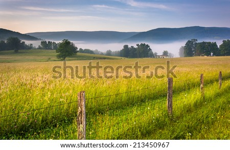 Farm field and distant mountains on a foggy morning in the rural Potomac Highlands of West Virginia. - stock photo