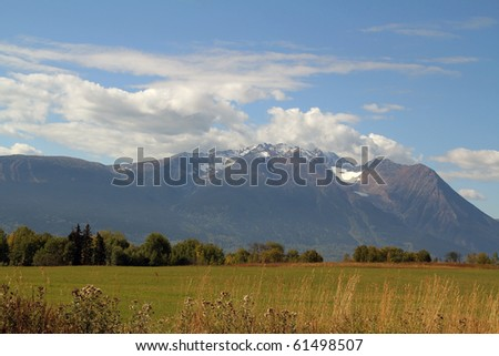 farm field with snow capped mountains, Smithers BC Canada - stock photo