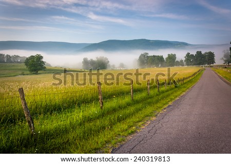 Farm fields along a country road on a foggy morning in the Potomac Highlands of West Virginia. - stock photo