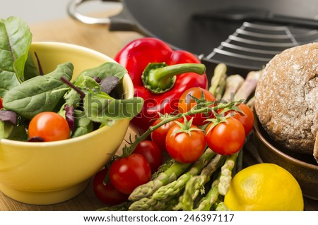 Farm fresh vegetables ready to be prepared for dinner with a red sweet bell pepper, tomatoes, lemon, asparagus spears, baby spinach for a salad and freshly baked brown rolls - stock photo