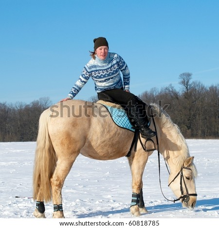 Farm girl sitting on horseback - stock photo