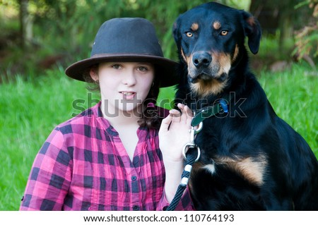 Farm girl with her working cattle dog on a farm in - stock photo