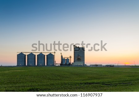 farm grain silos for agriculture after sunset - stock photo