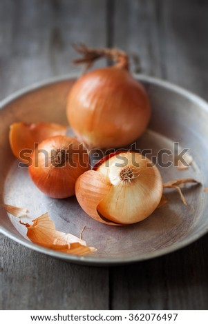Farm onions on a rustic metallic plate,shallow depth of field - stock photo