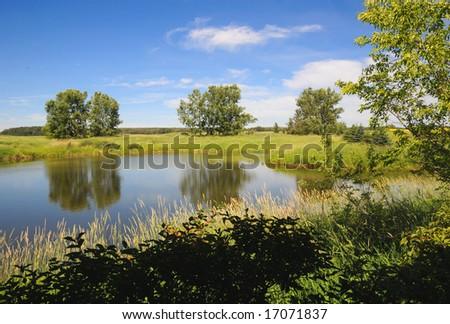 Farm pond in rural Alberta - stock photo