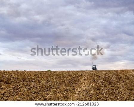 Farm tractor harrowing arable field - stock photo