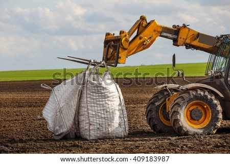 farm tractor in field with bags of potatoes or a truck with bags in the field - stock photo