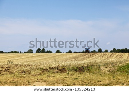 Farm tractor plowing the field. Riverhead, Long Island, New York. - stock photo