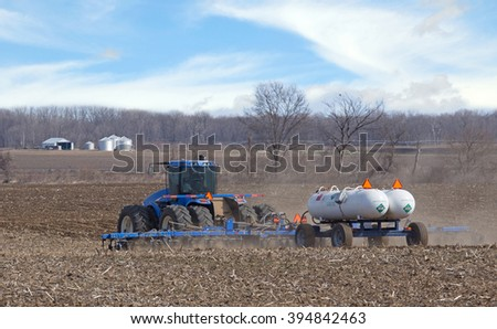 Farm tractor pulling anhydrous ammonia tanks fertilizing farmland - stock photo