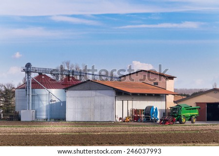 Farm with silos, various agricultural tools and thresher - stock photo