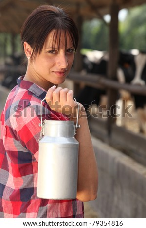 Farm worker holding milk container - stock photo