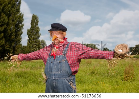 Farmer acting as a living scarecrow holding a bird's nest in his hand - stock photo