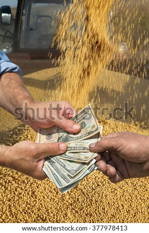 Farmer and buyer hands holding dollar banknote with soy bean crop in background - stock photo