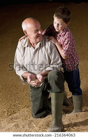 Farmer and grandson holding wheat grains - stock photo