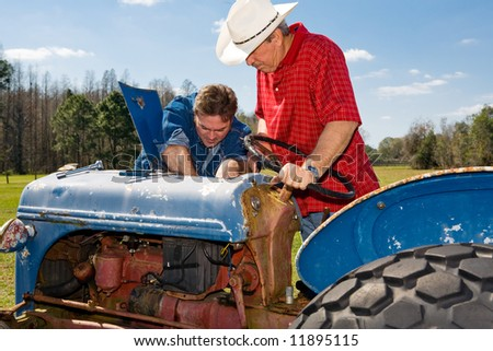 Farmer and ranch hand work on repairing the old tractor together. - stock photo