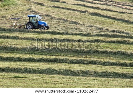 farmer and tractor while cutting grass in a meadow in the mountains - stock photo