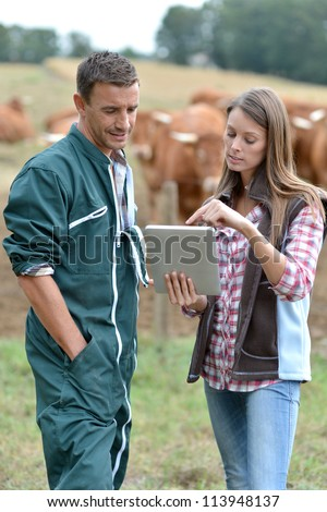 Farmer and woman in cow field using tablet - stock photo