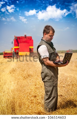 Farmer calculating earning in field - stock photo