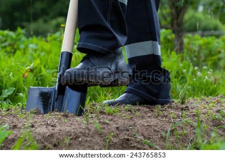Farmer digging a garden - closeup shot - stock photo