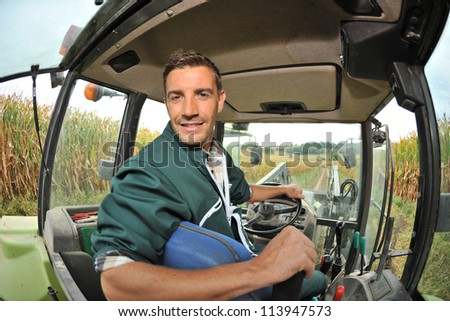 Farmer driving tractor in corn field - stock photo