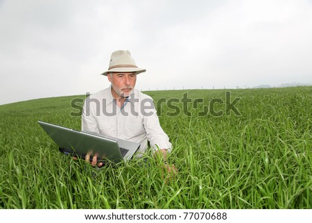 Farmer examining crop with laptop computer - stock photo