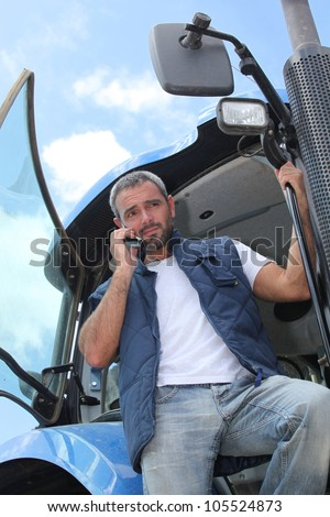 Farmer getting down from tractor with mobile phone - stock photo