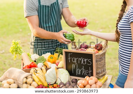 Farmer giving pepper to customer on a sunny day - stock photo