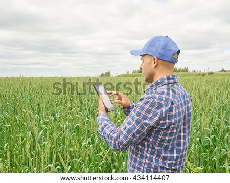 Farmer in a plaid shirt controlled his field and looking at tablet - stock photo