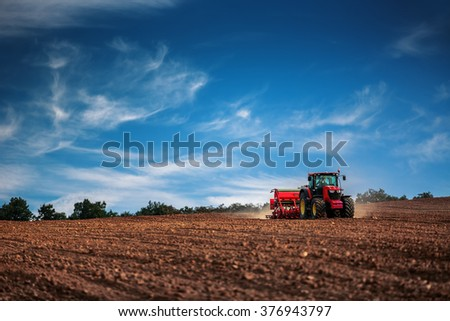 Farmer in tractor preparing farmland with seedbed for the next year - stock photo