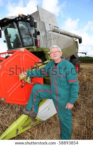 Farmer in wheat field in front of harvesting machine - stock photo