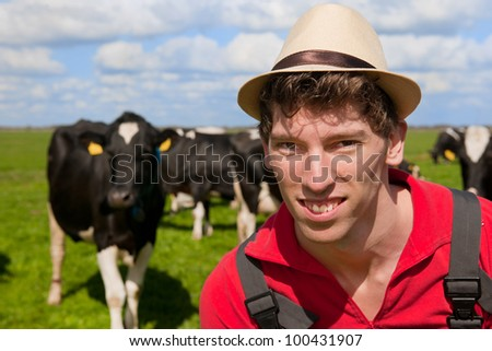 Farmer is looking at his cattle cows in the meadows - stock photo